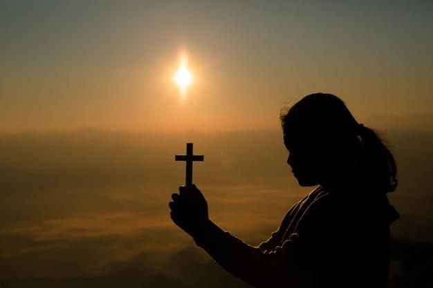 Adolescente tenant croix à prier. paix, espoir, concept de rêves. Photo gratuit