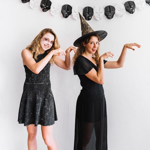 Des adolescentes en costumes d'halloween agissant comme des zombies Photo gratuit