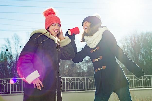 Adolescentes filles crier dans un gobelet en papier mégaphone Photo Premium