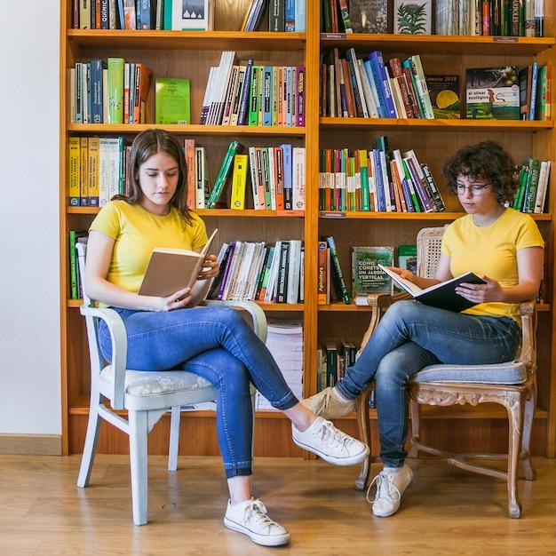 Adolescentes, lecture sur des chaises près de la bibliothèque Photo gratuit