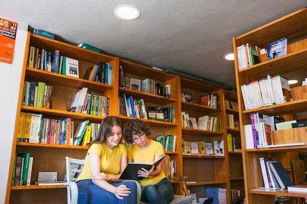 Adolescentes, lecture dans une bibliothèque confortable Photo gratuit