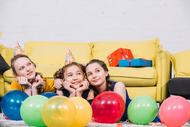Adolescentes réfléchies sur le tapis avec des ballons colorés dans le salon Photo gratuit