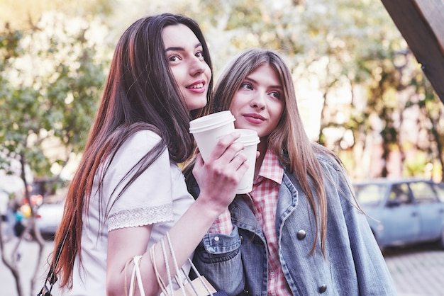 Adolescentes Souriantes Avec Des Tasses à Café Dans La Rue. Concept De Boissons Et D'amitié. Photo gratuit