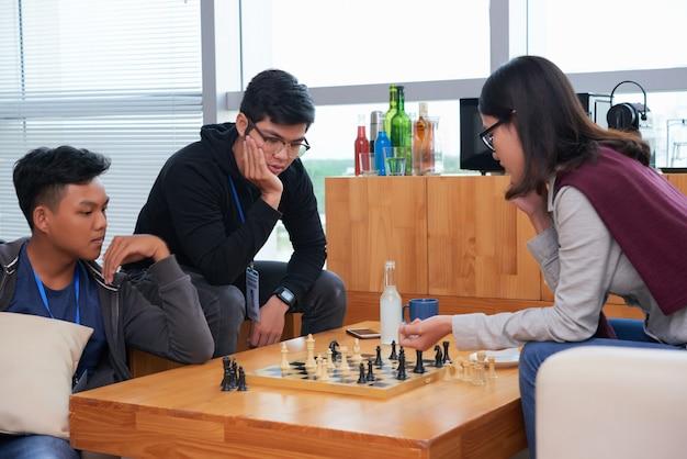 Les adolescents asiatiques jouent aux échecs avec leur ami en regardant le match Photo gratuit