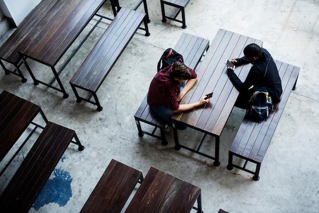 Des adolescents assis ensemble dans une cantine vide Photo gratuit