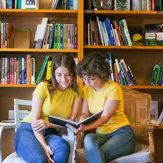 Adolescents sur des chaises en lisant le livre ensemble Photo gratuit