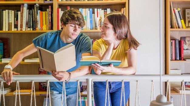 Adolescents communiquent en lisant dans la bibliothèque Photo gratuit