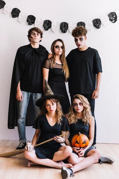 Des adolescents en costumes d'halloween avec balai et citrouille Photo gratuit
