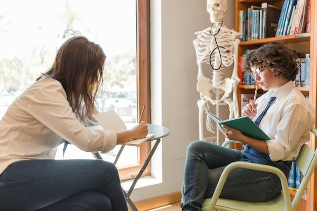 Adolescents à faire leurs devoirs à la bibliothèque Photo gratuit