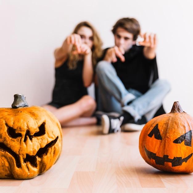 Des adolescents faisant des gestes de zombies derrière des citrouilles Photo gratuit