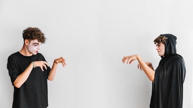 Adolescents en habits noirs et effrayants faisant des gestes de zombies Photo gratuit
