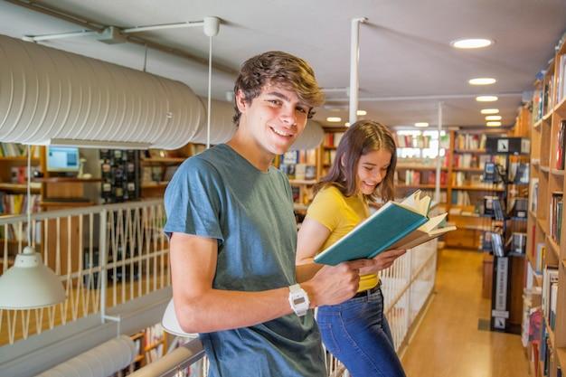 Adolescents joyeux, appréciant la lecture près de la balustrade Photo gratuit