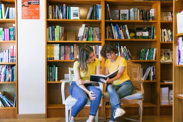 Adolescents, lecture de livre sur des chaises Photo gratuit