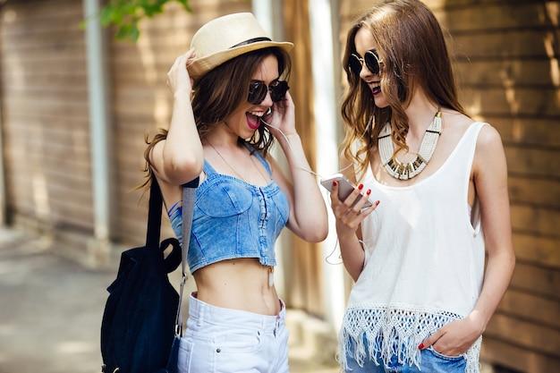 Les adolescents avec des lunettes de soleil en écoutant de la musique ensemble Photo gratuit
