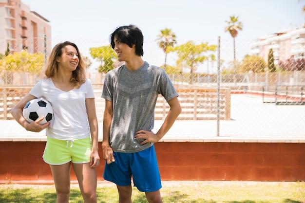 Adolescents multiethniques souriants se regardant en contexte urbain Photo gratuit
