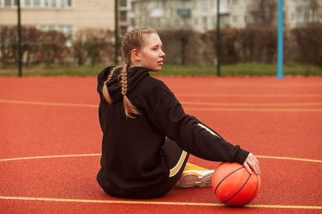 Adolescents Posant Sur Le Terrain De Basket Photo gratuit