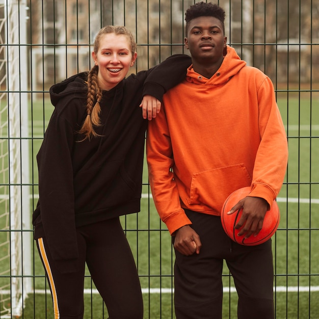 Adolescents Posant Sur Le Terrain De Basket Photo gratuit