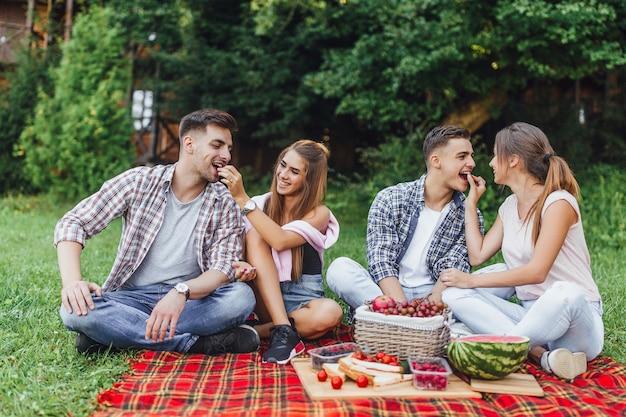 Les Adolescents S'amusent. Des Filles Et Des Garçons Joyeux Passent Le Week-end En Plein Air à Pique-niquer Et à Manger Des Fruits Photo Premium