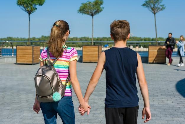 Adolescents, tenant les mains vue arrière. amitié, premier amour. Photo Premium
