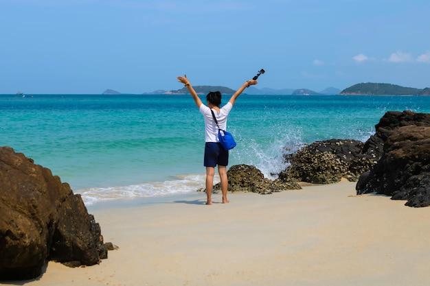 Adoptez la vue arrière de la jeune fille avec une caméra pour vous détendre en dehors de la plage et regardez la vue sur la mer à l'île samsan de chonburi, en thaïlande. Photo Premium