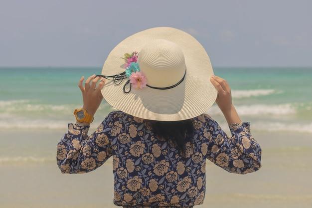 Adoptez la vue arrière de la jeune fille coiffée d'un chapeau pour vous détendre en dehors de la plage et admirez la vue sur la mer à sattaheeb, en thaïlande. Photo Premium