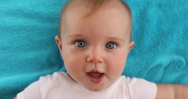 Adorable bébé aux yeux bleus, bouche ouverte, allongé sur une serviette bleue et regardant la caméra Photo Premium