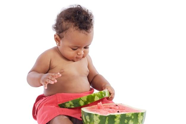 Adorable bébé manger une pastèque sur fond blanc Photo Premium