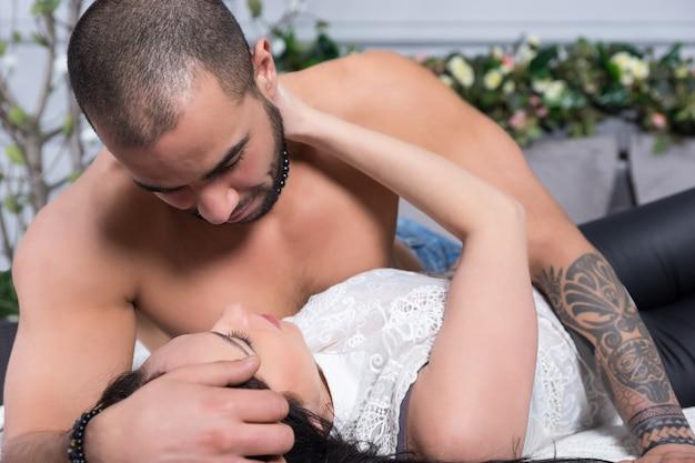 Adorable Couple International D'homme à La Poitrine Nue, Les Mains Tatouées Et La Femme Brune Se Regardent En Position Couchée Sur Le Lit Douillet Gris Dans La Chambre Photo Premium