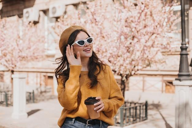 Adorable Femme à Lunettes, Béret Agite Sa Main Et Tient Un Verre De Café. Jolie Dame à Lunettes De Soleil Posant Avec Une Tasse De Thé Contre Sakura Photo gratuit
