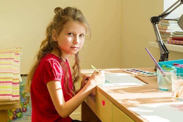 Adorable fille dessine l'aquarelle à la table de la maison Photo Premium