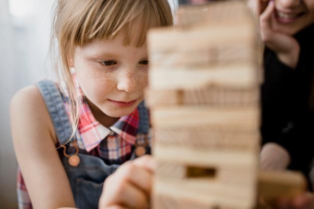 Adorable fille jouant jenga Photo gratuit