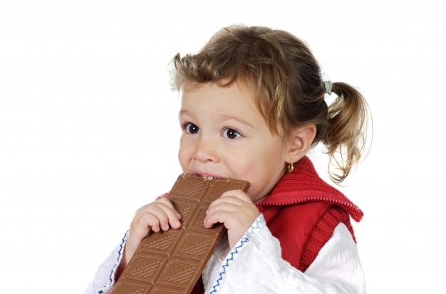Adorable fille mangeant du chocolat sur fond blanc Photo Premium