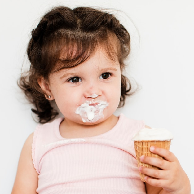 Adorable fille mangeant de la glace Photo gratuit