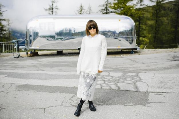 Adorable fille sur la route de haute montagne près de la voiture Photo gratuit