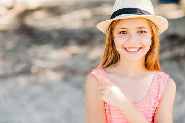 Adorable fille souriante pointant du doigt regardant la caméra en plein jour Photo gratuit