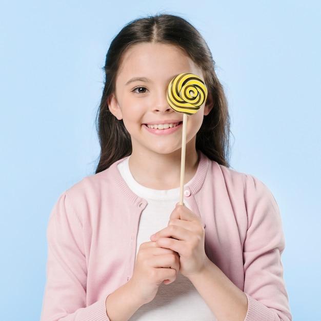 Adorable fille en studio tenant la sucette Photo gratuit