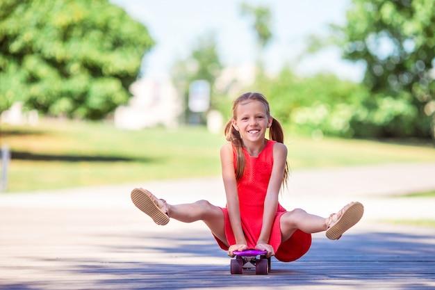 Adorable gamin d'équitation skateboard dans le parc de l'été. Photo Premium