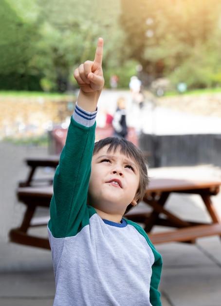 Adorable garçon pointant son doigt vers le ciel avec une lumière brillante du soleil le matin Photo Premium