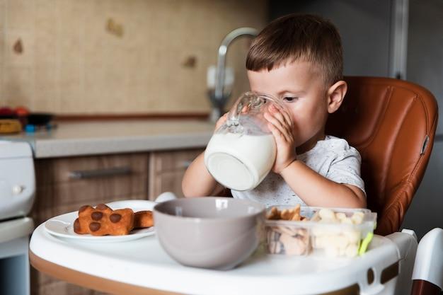Adorable jeune garçon buvant du lait Photo gratuit