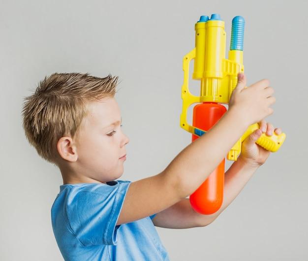 Adorable Jeune Garçon Jouant Avec Un Pistolet à Eau Photo gratuit