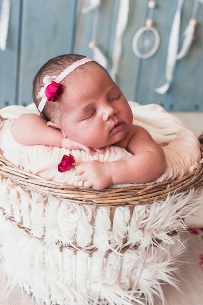 Adorable petit bébé dort dans le panier Photo gratuit