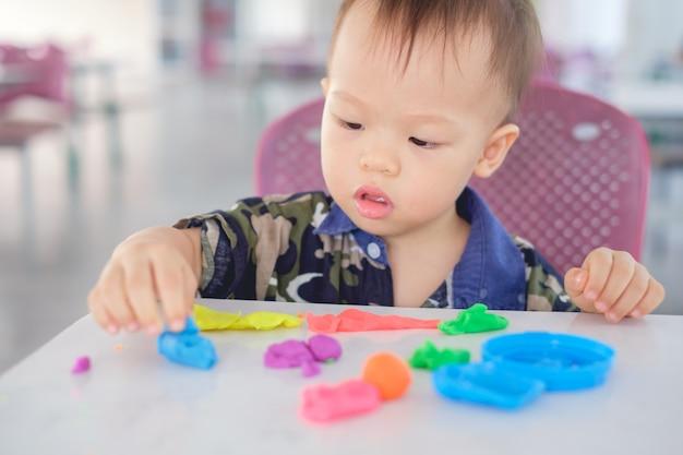 Adorable petit garçon asiatique de 18 mois, enfant de garçon de bébé, s'amusant à jouer de la pâte à modeler colorée / jeu de la dought au jeu école / garde d'enfants, jouets éducatifs pour enfant concept de jeu créatif pour les tout-petits Photo Premium