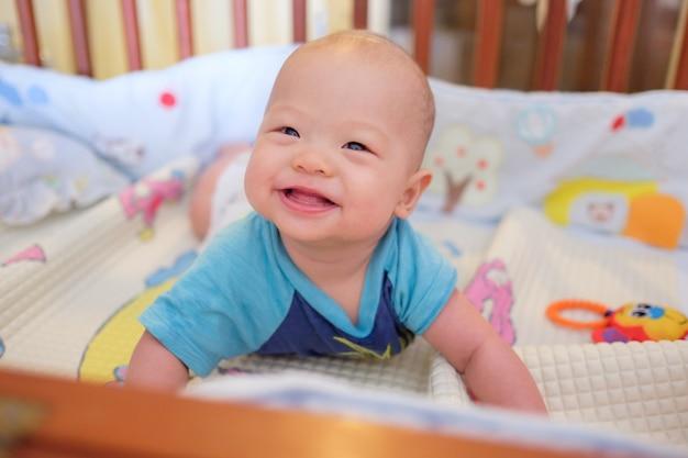 Adorable petit garçon asiatique de 5 à 6 mois dans le berceau dans la chambre à la maison; nouveau-né relaxant. garderie pour les jeunes enfants. mise au point douce et sélective Photo Premium