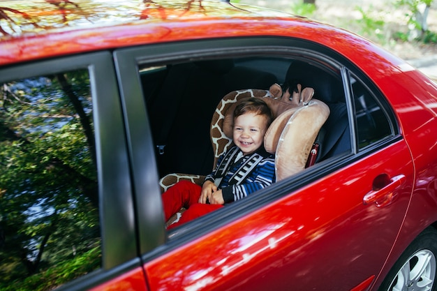 Adorable Petit Garçon Assis Dans Un Siège Auto. Photo Premium
