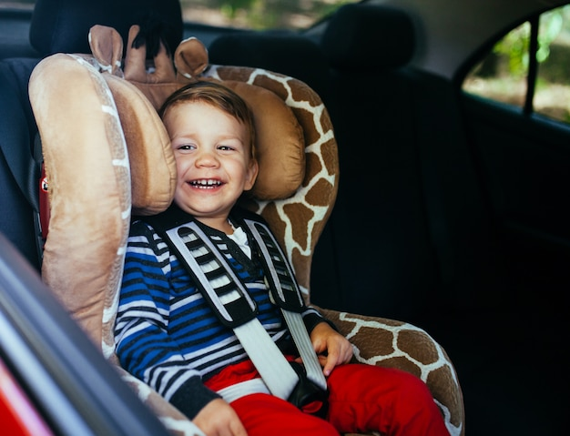 Adorable petit garçon dans un siège auto. Photo Premium