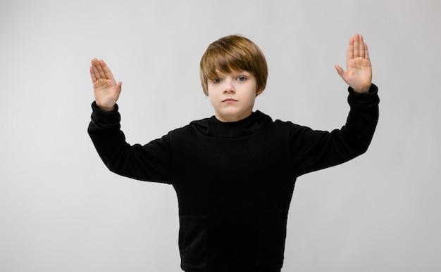 Adorable petit garçon sérieux debout avec les mains Photo Premium