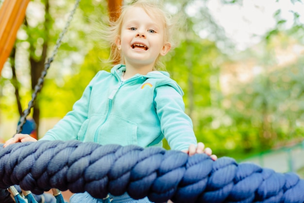 Adorable Petite Fille De 4 Ans S'amusant Sur Une Balançoire Ronde En Corde Dans Une Aire De Jeux Pendant La Journée D'été. Photo Premium
