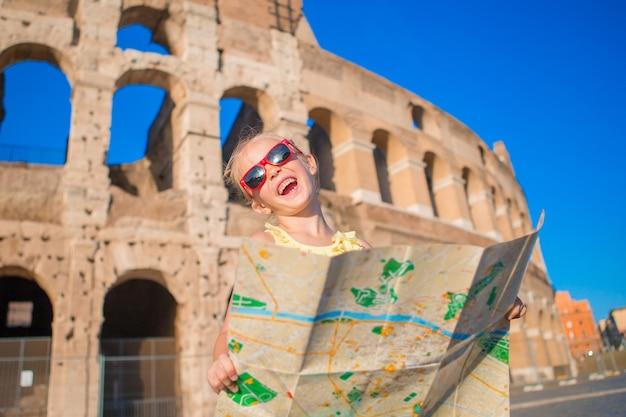 Adorable petite fille active avec une carte devant le colisée à rome, en italie. Photo Premium