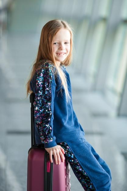 Adorable petite fille à l'aéroport avec ses bagages en attente d'embarquement Photo Premium
