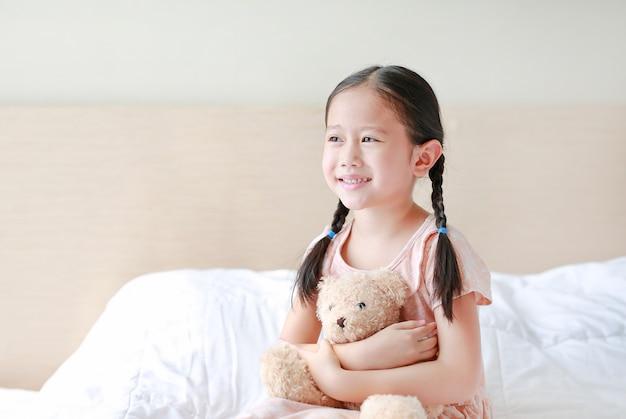 Adorable petite fille asiatique embrassant un ours en peluche assis sur le lit à la maison. Photo Premium